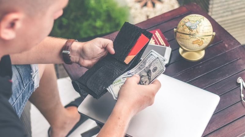 Man holding his wallet and paper bills